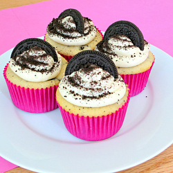 white cake oreo cupcakes with a whole cookie at the bottom and cream cheese frosting
